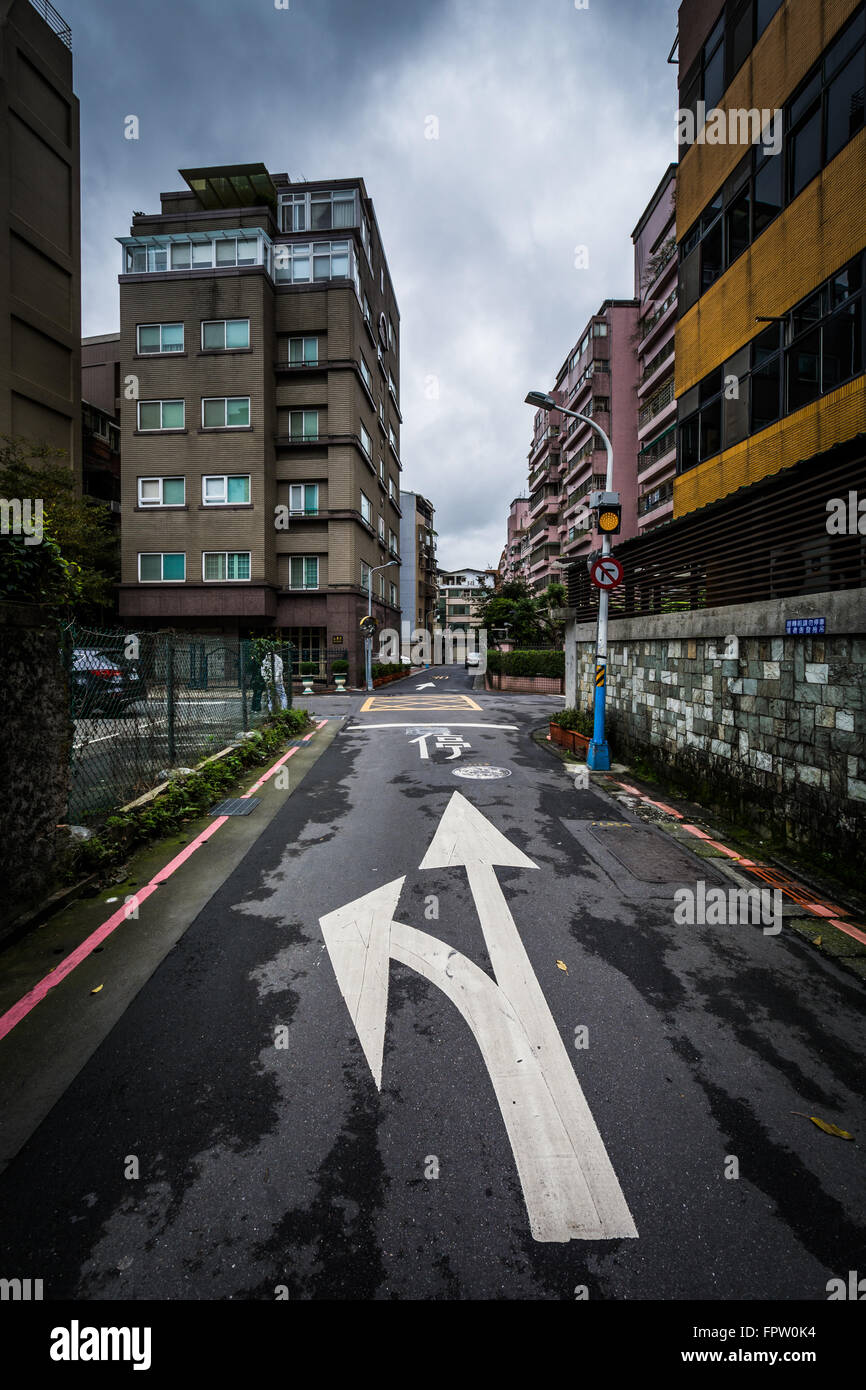 Arrow on the pavement of a narrow street in the Da'an District, in Taipei, Taiwan. - Stock Image