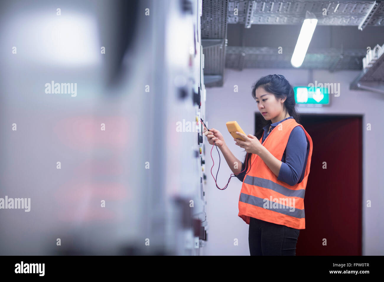 Young female engineer examining control panel with multimeter in an industrial plant, Baden-Württemberg, Germany - Stock Image