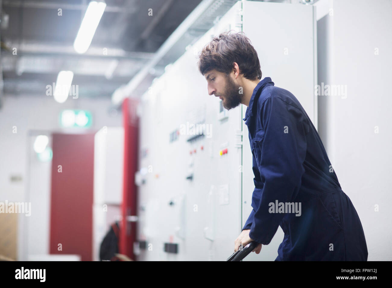 Young male engineer pushing cart in an industrial plant, Freiburg Im Breisgau, Baden-Württemberg, Germany - Stock Image
