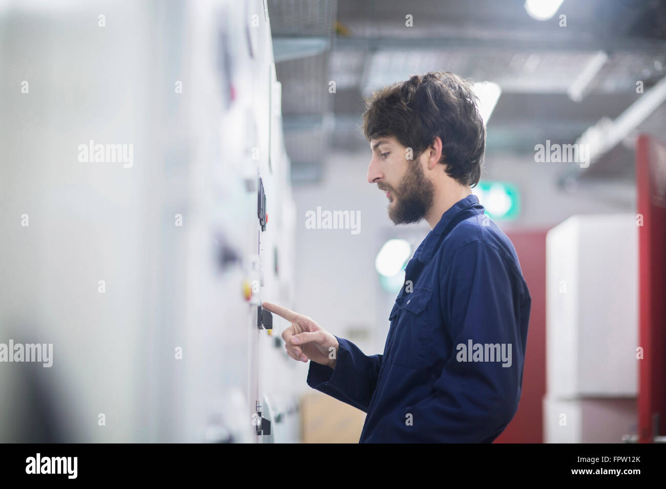 Young male engineer controlling a switch gear in control room, Freiburg Im Breisgau, Baden-Württemberg, Germany - Stock Image