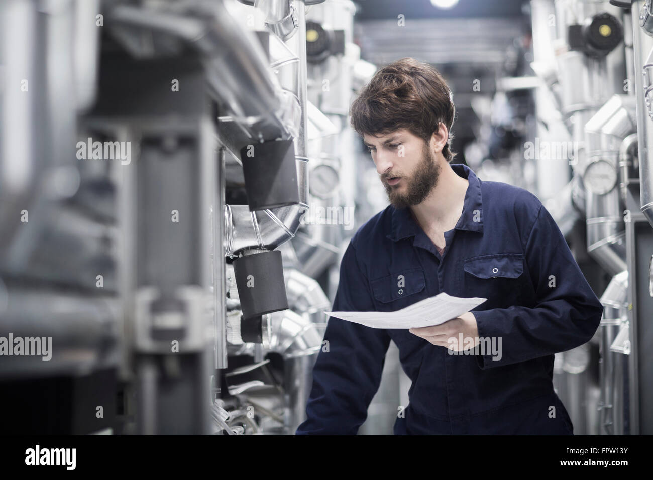 Young male engineer working in an industrial plant, Freiburg Im Breisgau, Baden-Württemberg, Germany - Stock Image