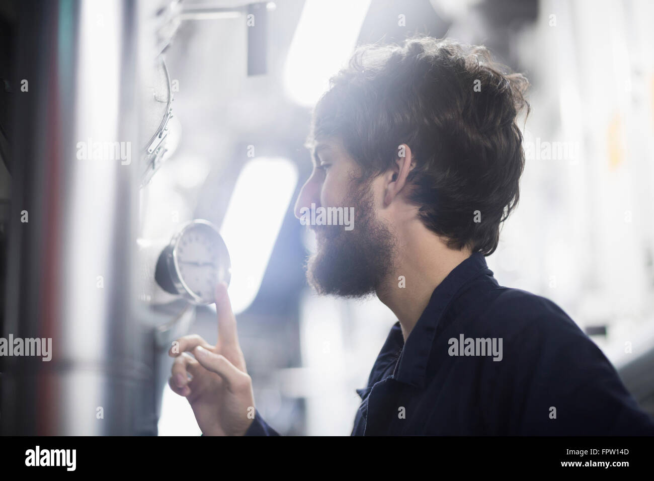 Young male engineer examining gauge in an industrial plant, Freiburg Im Breisgau, Baden-Württemberg, Germany - Stock Image