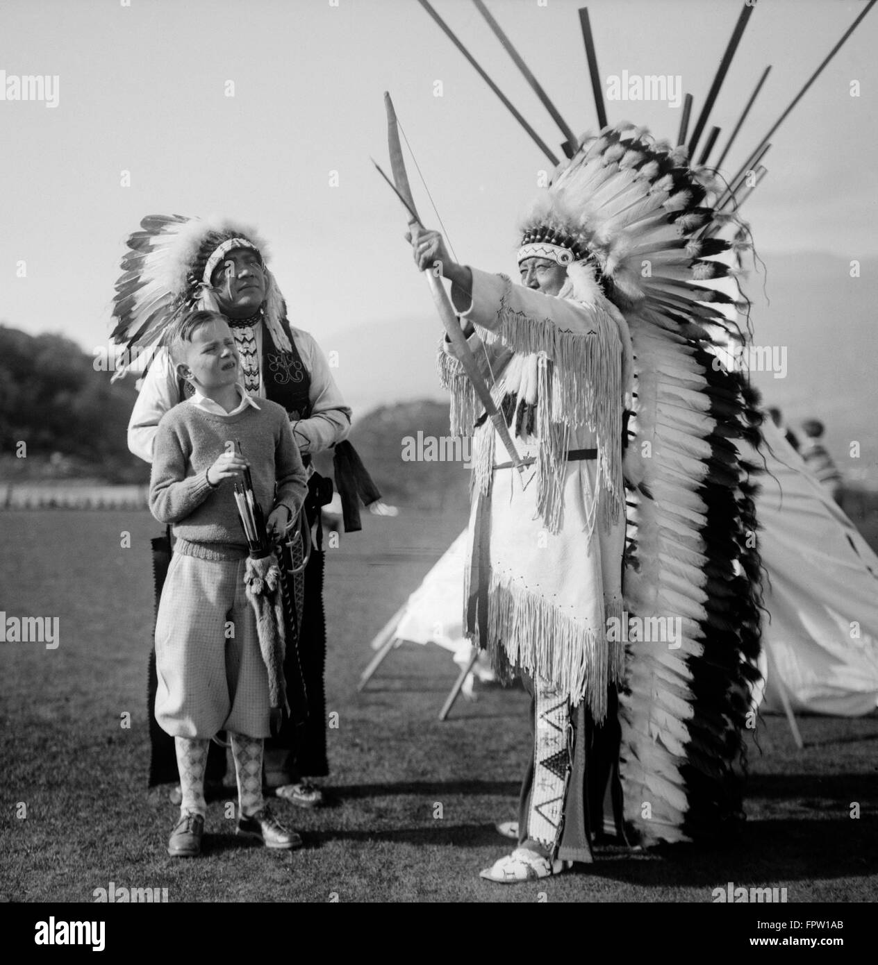 e13a03f2a1 1930s TWO NATIVE AMERICAN INDIAN MEN WEARING TRADITIONAL CLOTHING FEATHER  HEADDRESSES CHIEF SHOWING BOY HOW TO