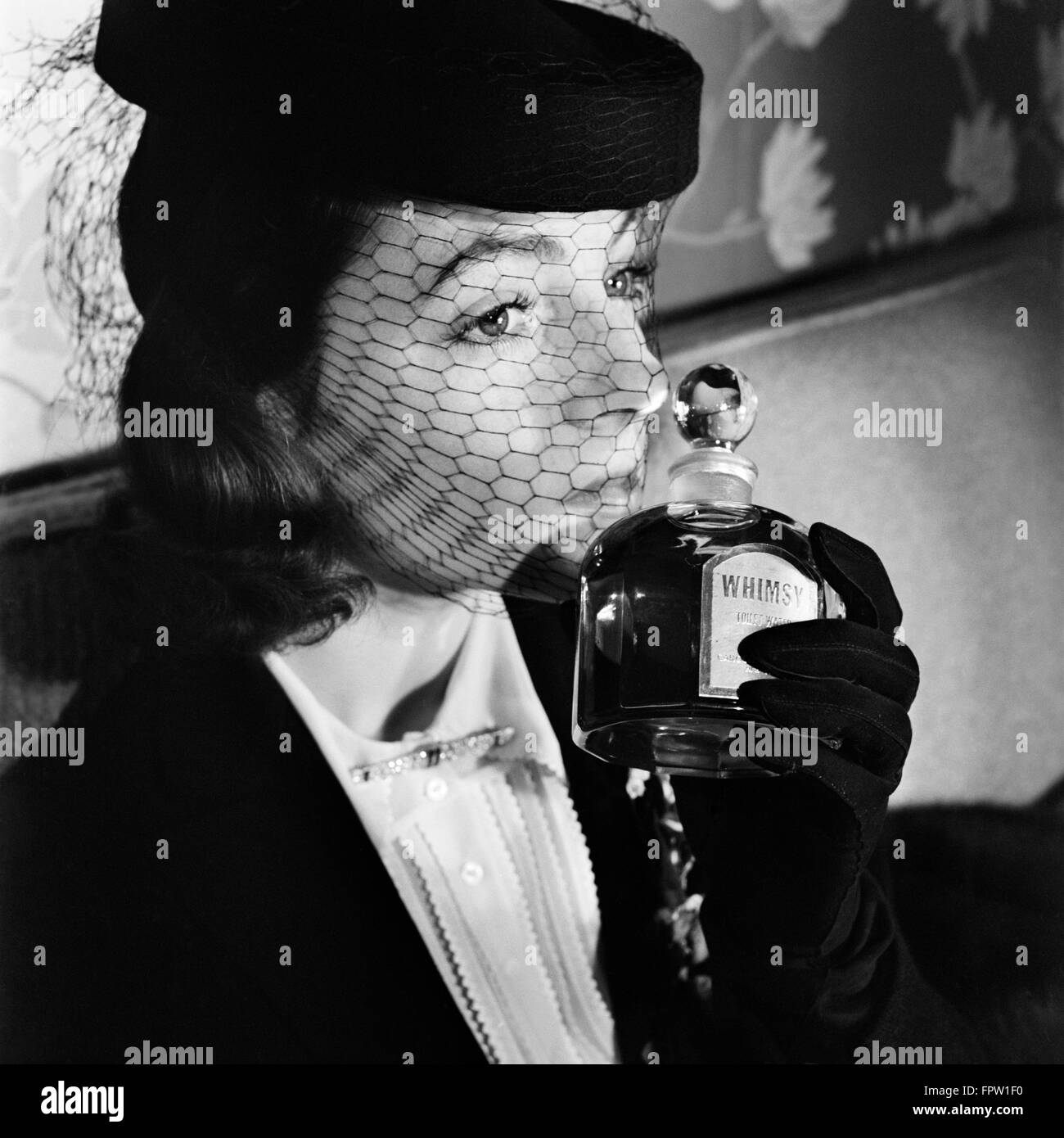 1930s 1940s ELEGANT UPSCALE WOMAN WEARING HAT WITH VEIL SNIFFING BOTTLE OF  WHIMSY PERFUME c82684ff3df