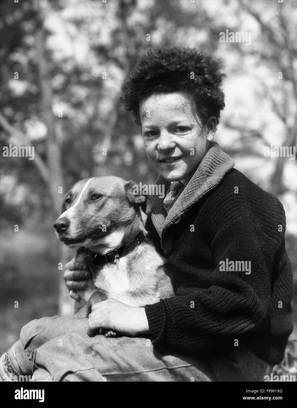 1920s 1930s SMILING BOY LOOKING AT CAMERA HOLDING DOG - Stock Image