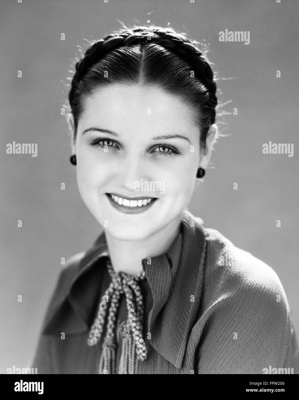 1930s SMILING PRETTY BRUNETTE WOMAN PORTRAIT HAIR BRAIDED LOOKING AT CAMERA - Stock Image