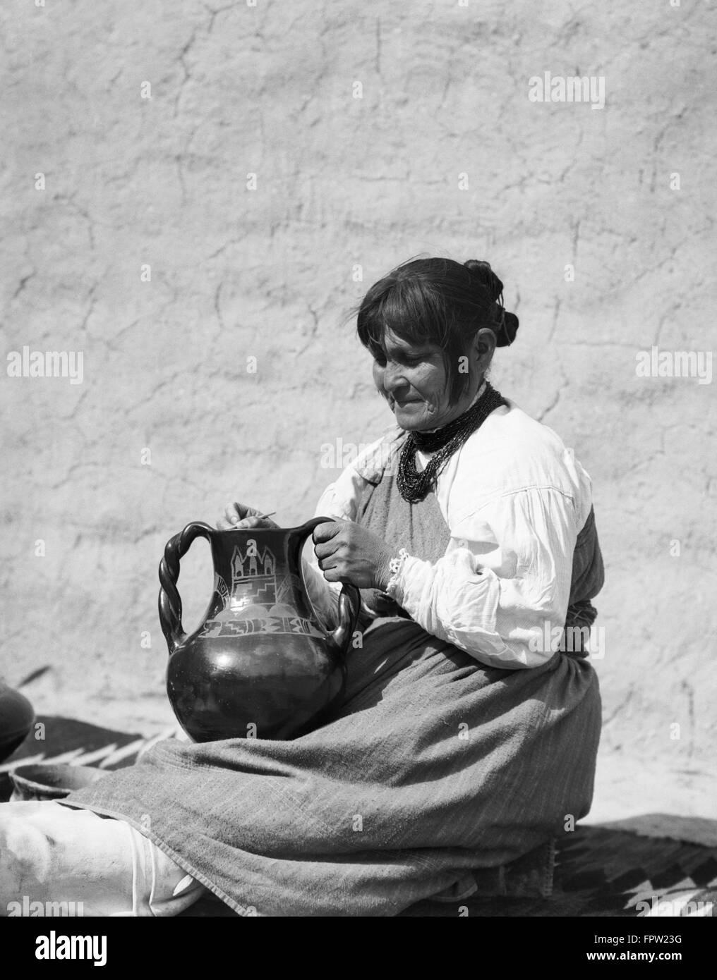 1930s NATIVE AMERICAN INDIAN WOMAN POLISHING PIECE OF POTTERY SANTA CLARA PUEBLO NEW MEXICO USA - Stock Image