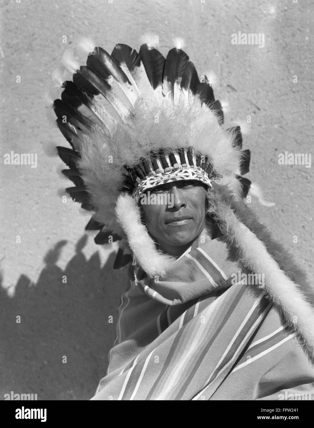 1930s PORTRAIT NATIVE AMERICAN INDIAN MAN WEARING FULL FEATHERED HEADDRESS WAR BONNET SAN ILDEFONSO PUEBLO NEW MEXICO - Stock Image