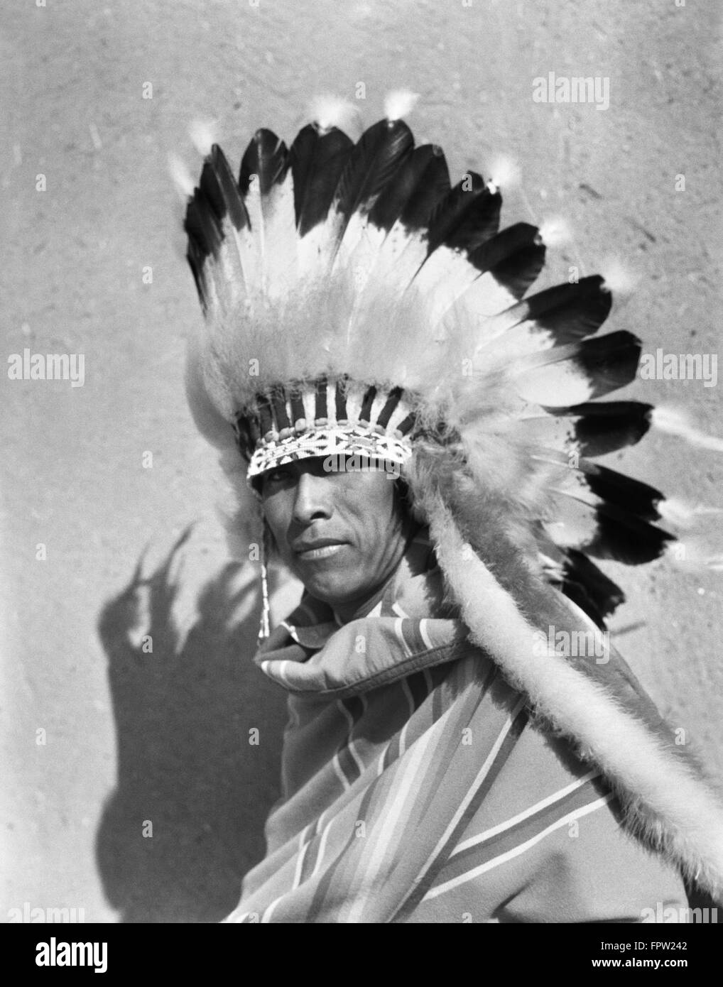 1930s NATIVE AMERICAN MAN WEARING FULL FEATHERED HEADDRESS WAR BONNET LOOKING AT CAMERA SAN ILDEFONSO PUEBLO NEW - Stock Image