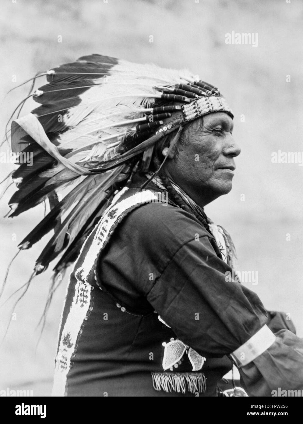 1920s PROFILE PORTRAIT NATIVE AMERICAN INDIAN MAN OF BLACKFOOT TRIBE WEARING FULL FEATHER HEADDRESS MONTANA USA - Stock Image