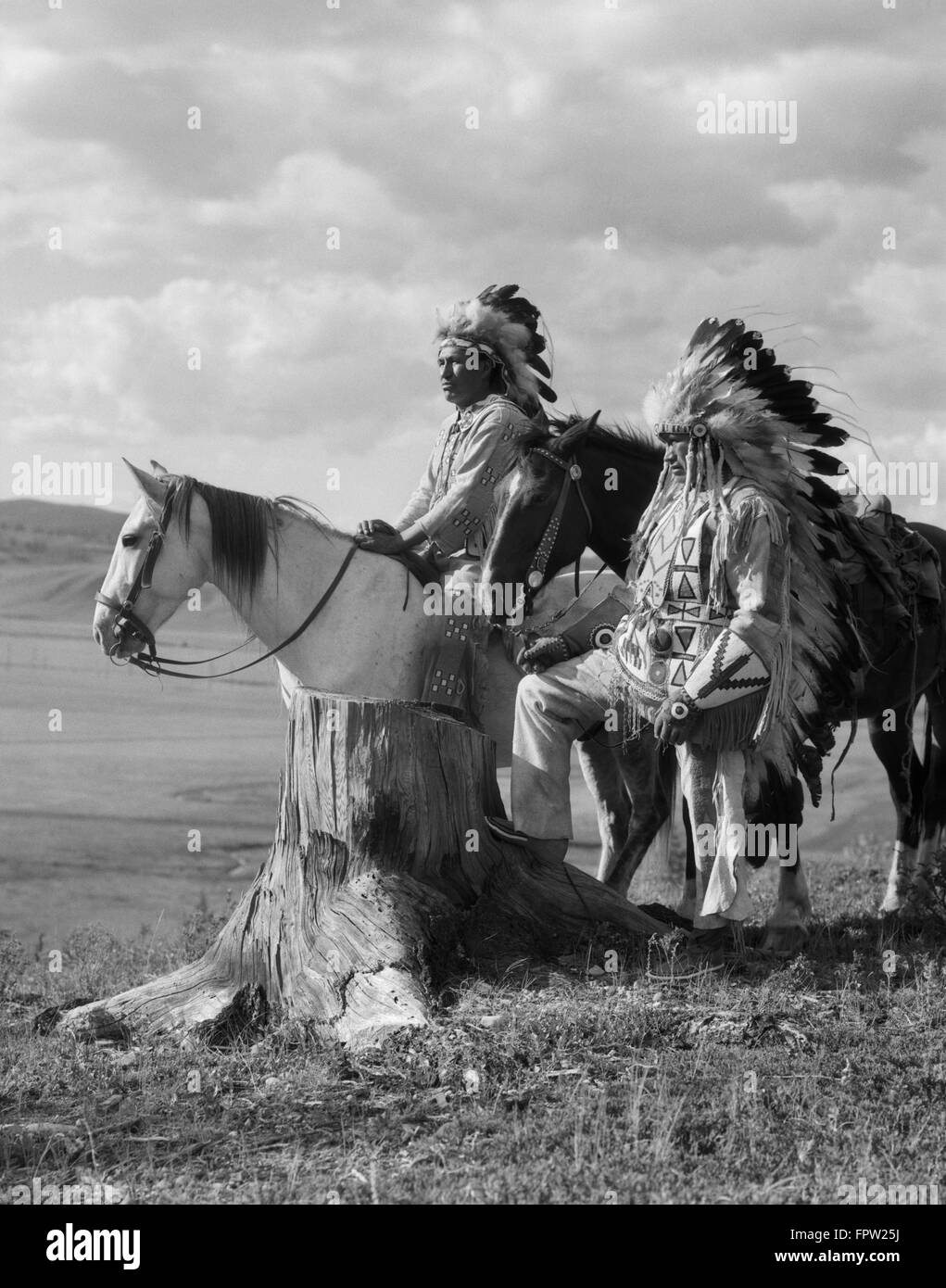 1920s TWO NATIVE AMERICAN STONEY SIOUX INDIAN MEN IN FULL FEATHER WAR BONNETS STANDING WITH HORSES ALBERTA CANADA - Stock Image