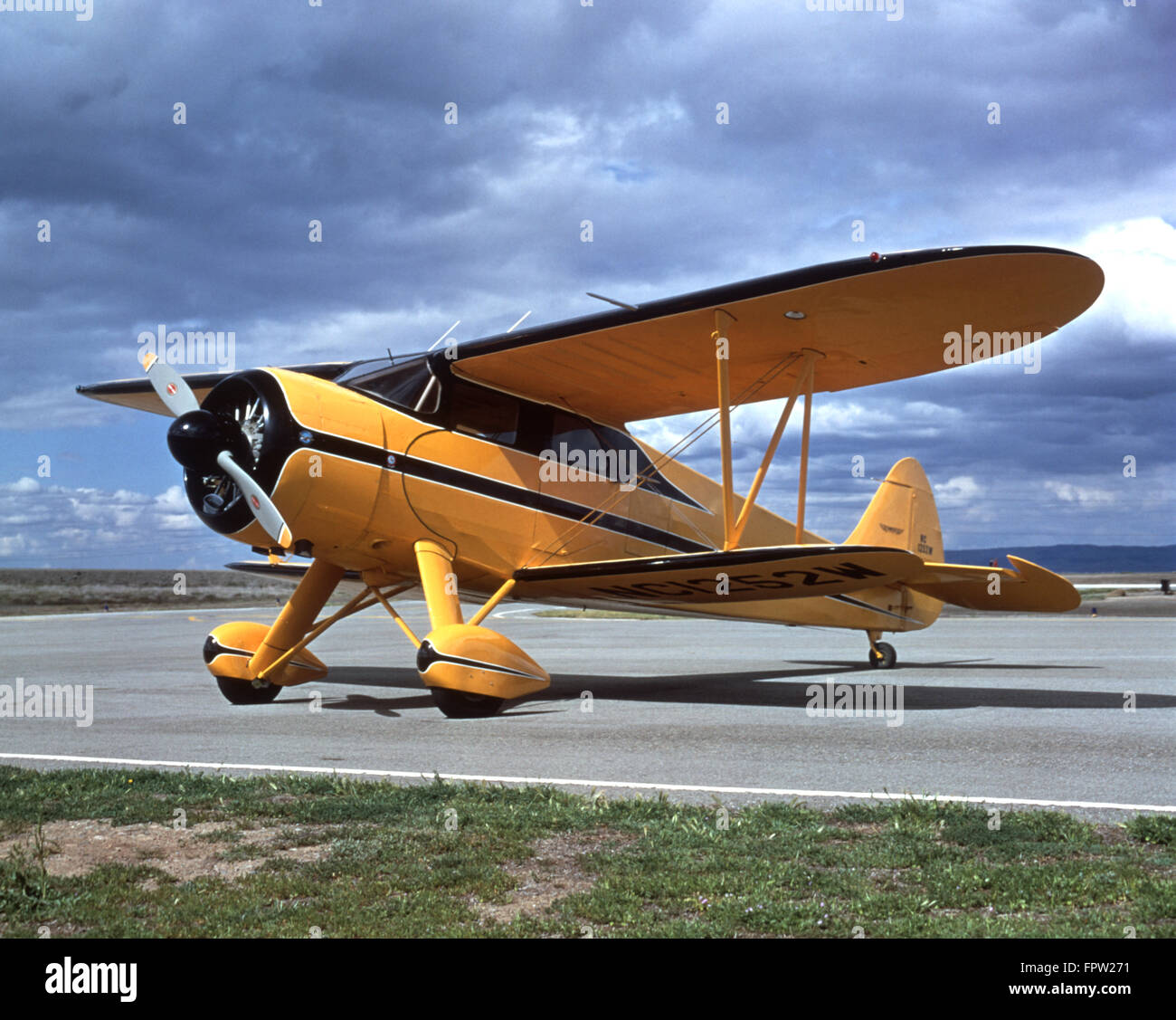 AIRPLANE YELLOW AND BLACK BI-PLANE  ON AIRPORT TARMAC - Stock Image