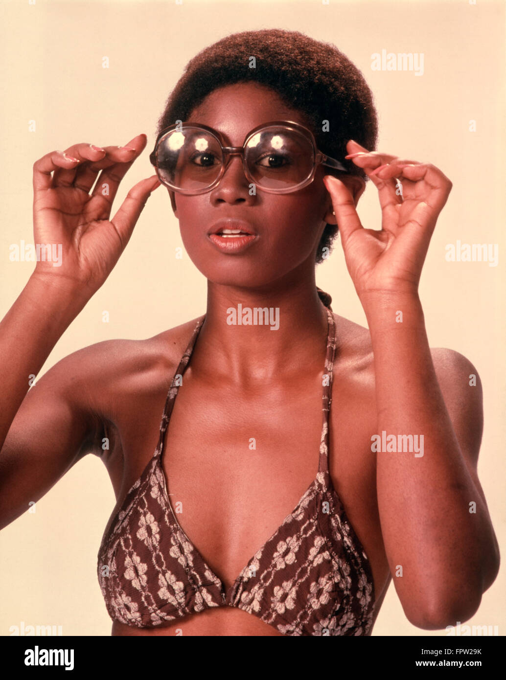 1970s AFRICAN AMERICAN WOMAN WEARING BIKINI BATHING SUIT TOP PUTTING ON LARGE LENS SUNGLASSES LOOKING AT CAMERA - Stock Image