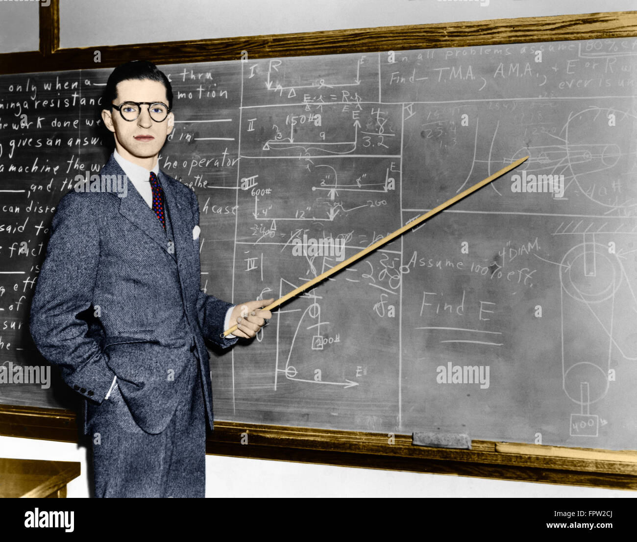 1930s 1940s MAN TEACHER PROFESSOR POINTING POINTER AT BLACKBOARD LOOKING AT CAMERA - Stock Image