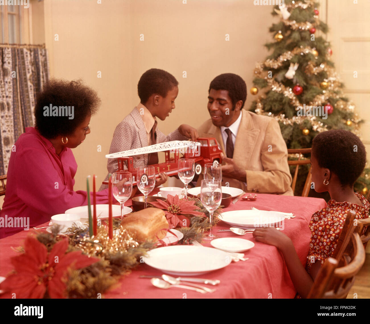 1970s AFRICAN AMERICAN FAMILY AT CHRISTMAS HOLIDAY DINNER TABLE FATHER MOTHER SON AND DAUGHTER - Stock Image