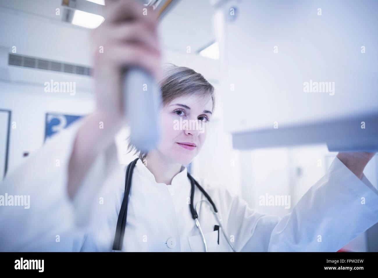 Young female doctor using x-ray machine in hospital, Freiburg im Breisgau, Baden-Württemberg, Germany - Stock Image