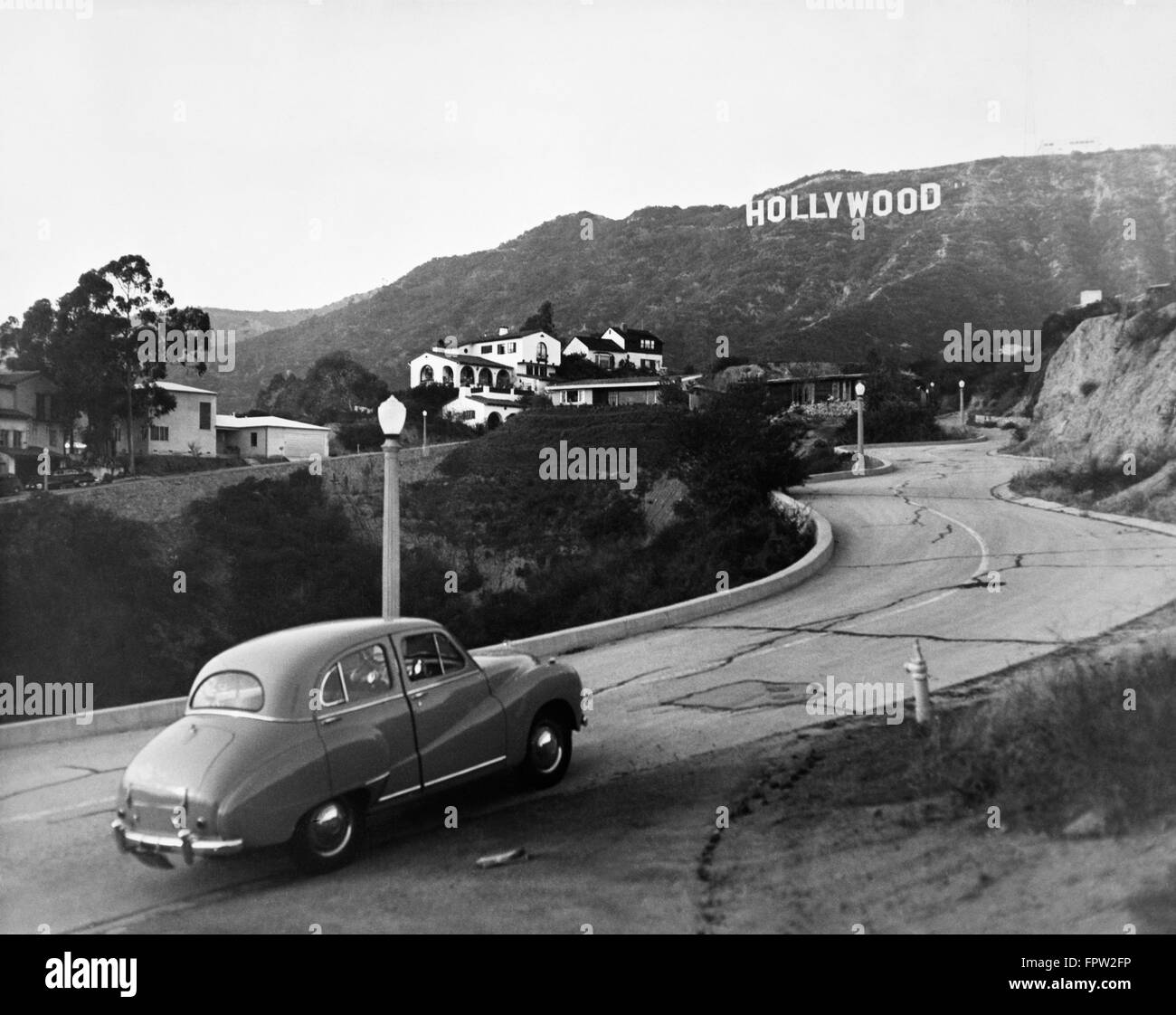 1950s AUSTIN CAR DRIVING UP THE HOLLYWOOD HILLS WITH SIGN IN DISTANCE