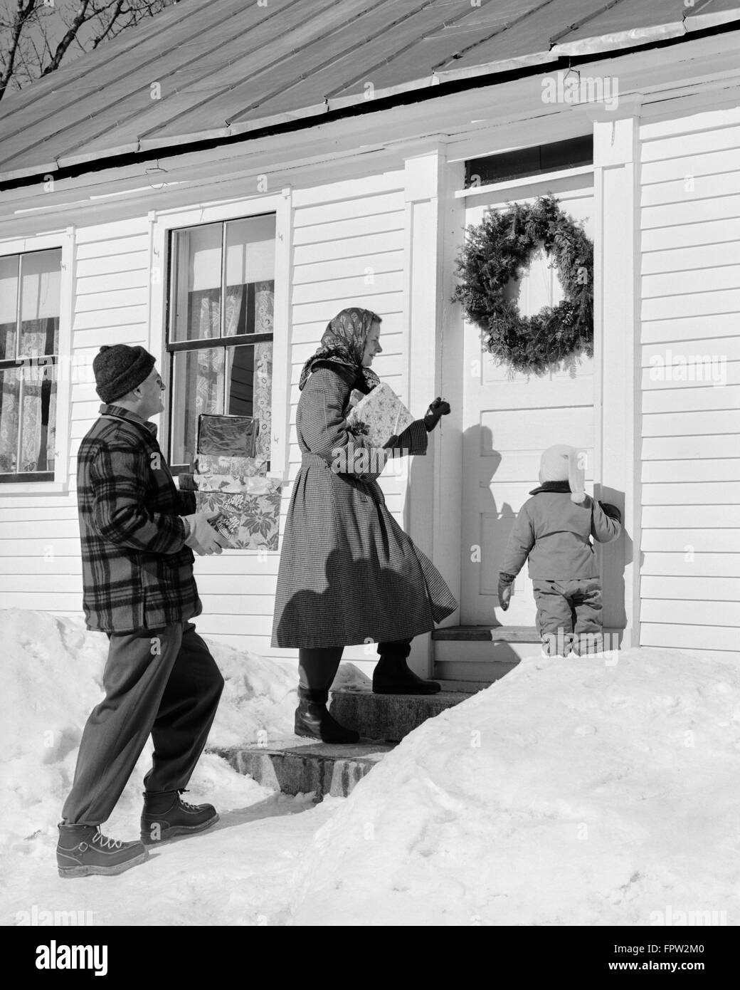 1950s 1960s Family At Front Door Carrying Christmas Gifts Stock