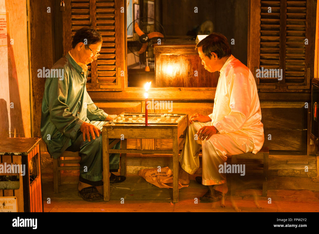 Men playing at the light of a candle a board game, Old Town of Hoi An, Vietnam Stock Photo