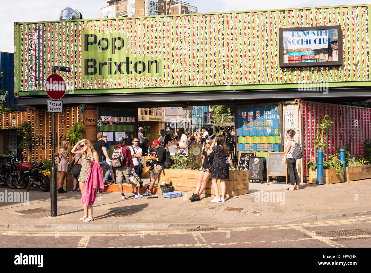 People enjoying the London summer in a new pop-up opened in Brixton called 'Pop Brixton'. - Stock Image