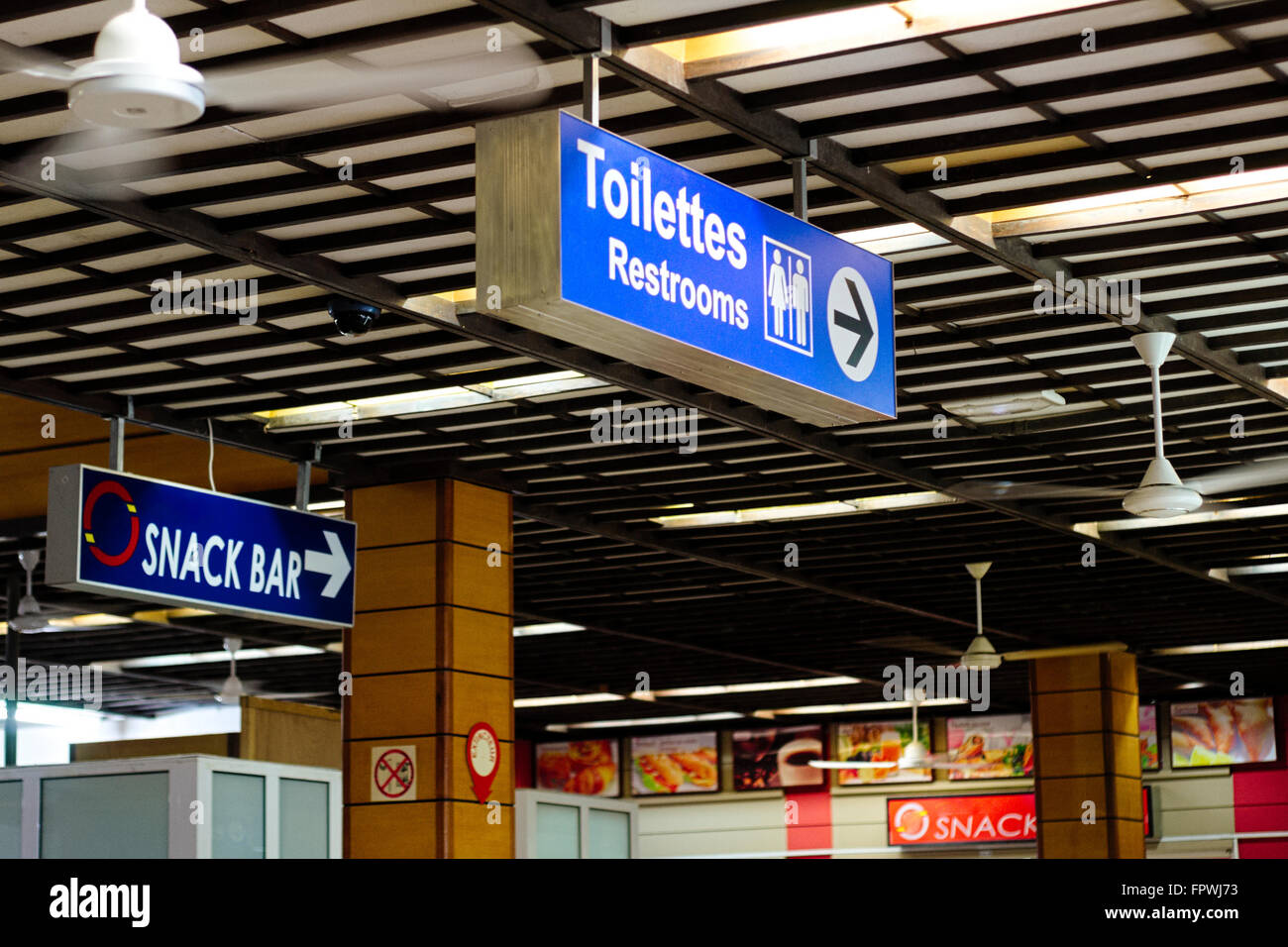 Airport ceiling with toilette and snack bar sign - Stock Image