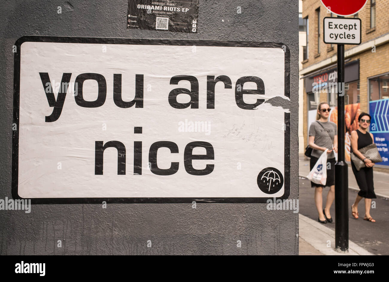 White billboard with the words 'You are nice' on a wall in a street in London. Two woman with sunglasses - Stock Image