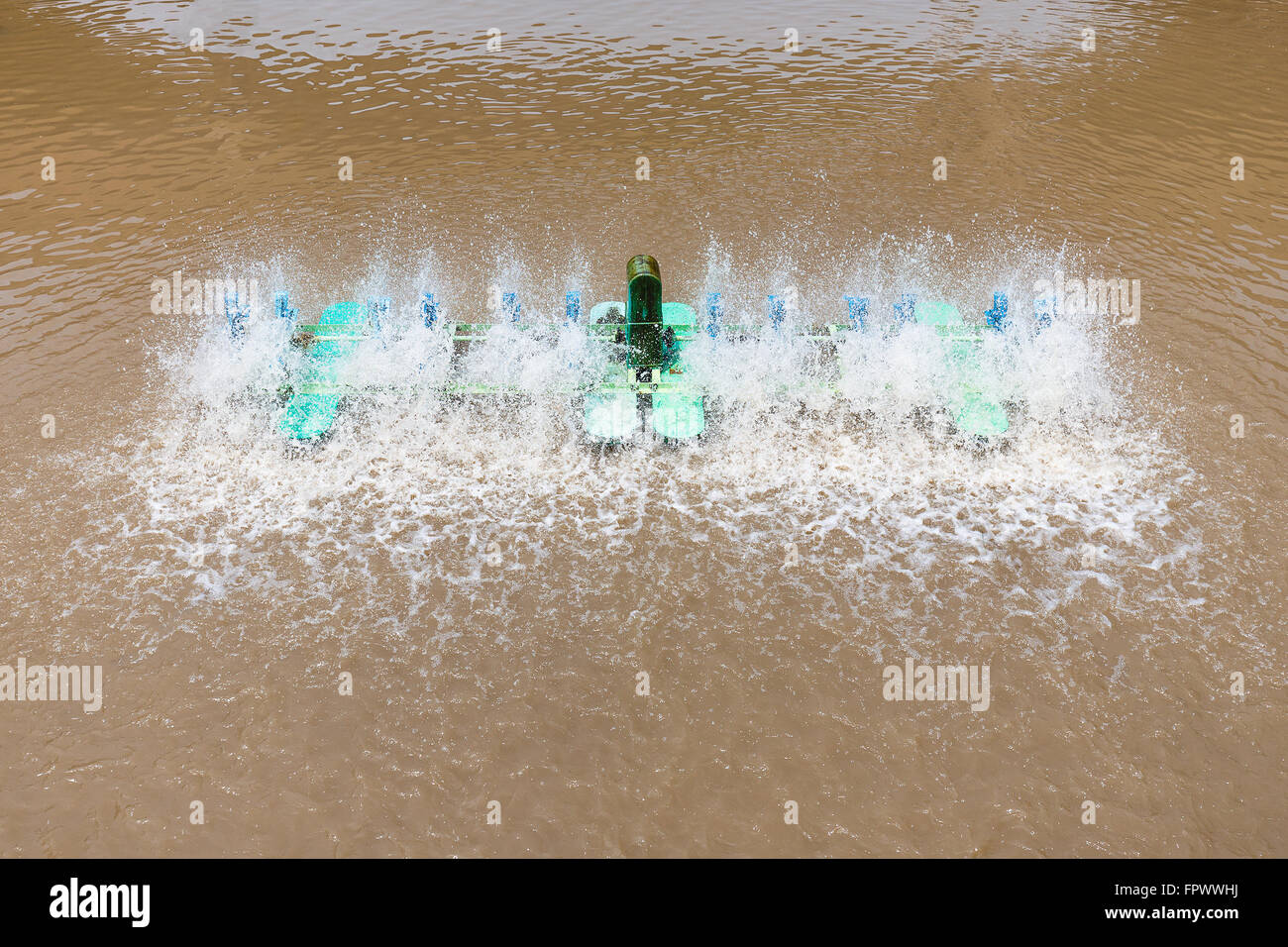 Waste water treatment machine spin on dark brown water - Stock Image