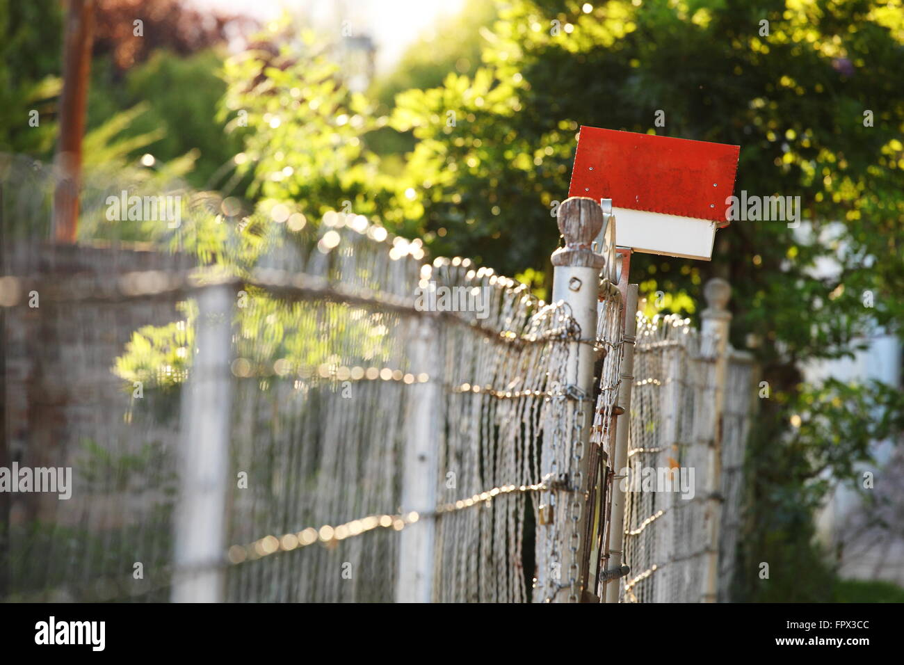 Red postbox on a rustic metal fence - Stock Image