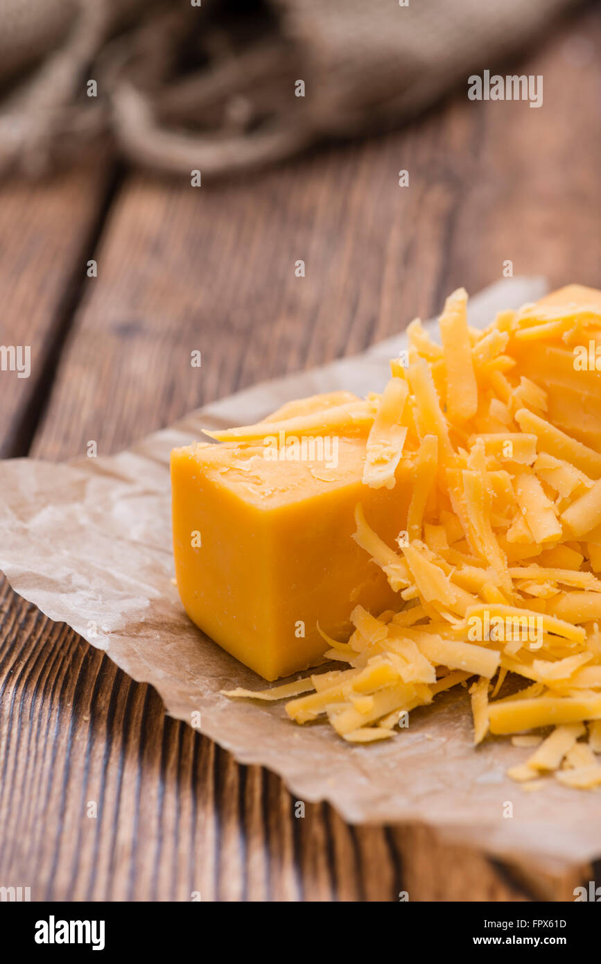 Grated Cheddar Cheese on rustic wooden background - Stock Image