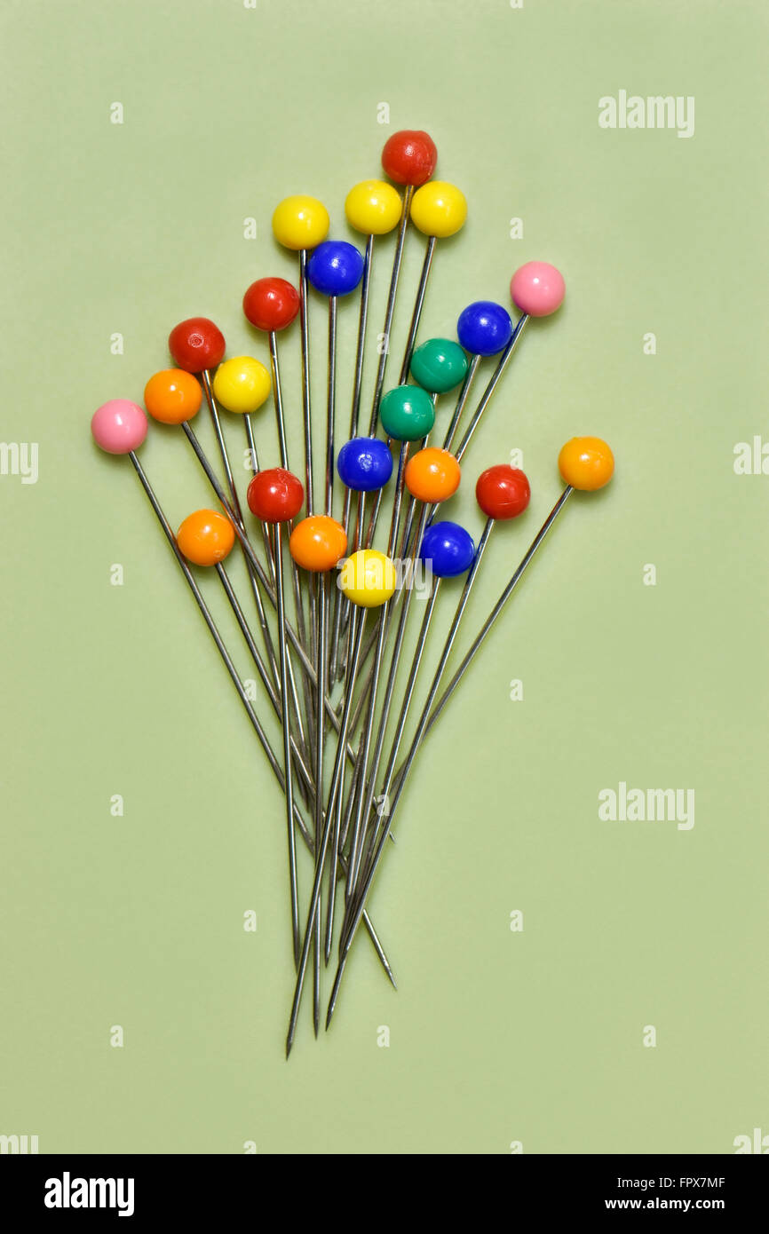 Colourful berry pins on green background in shape of a bunch of flowers - Stock Image