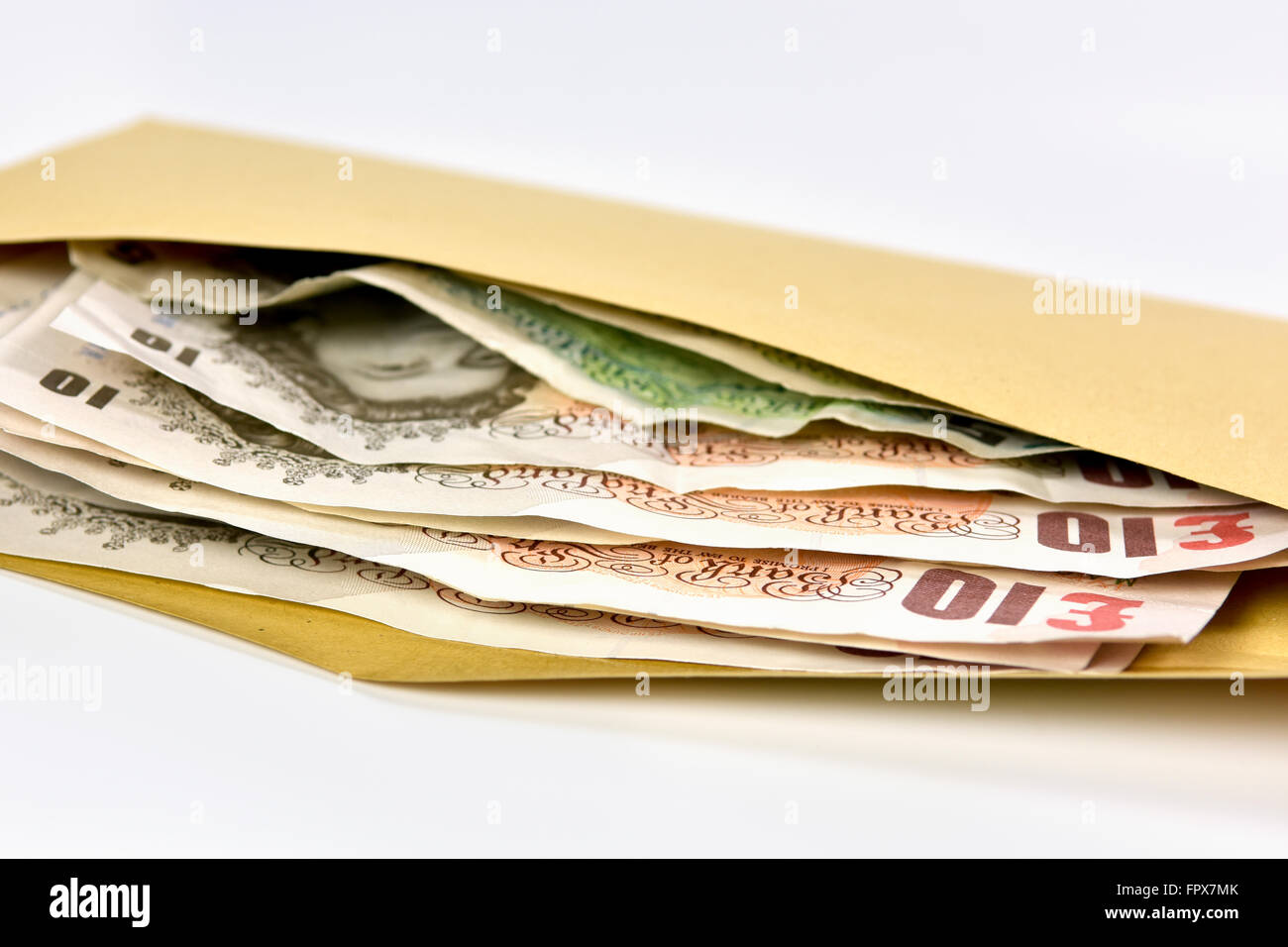 Wad of bank notes in British Sterling currency in brown envelope - Stock Image