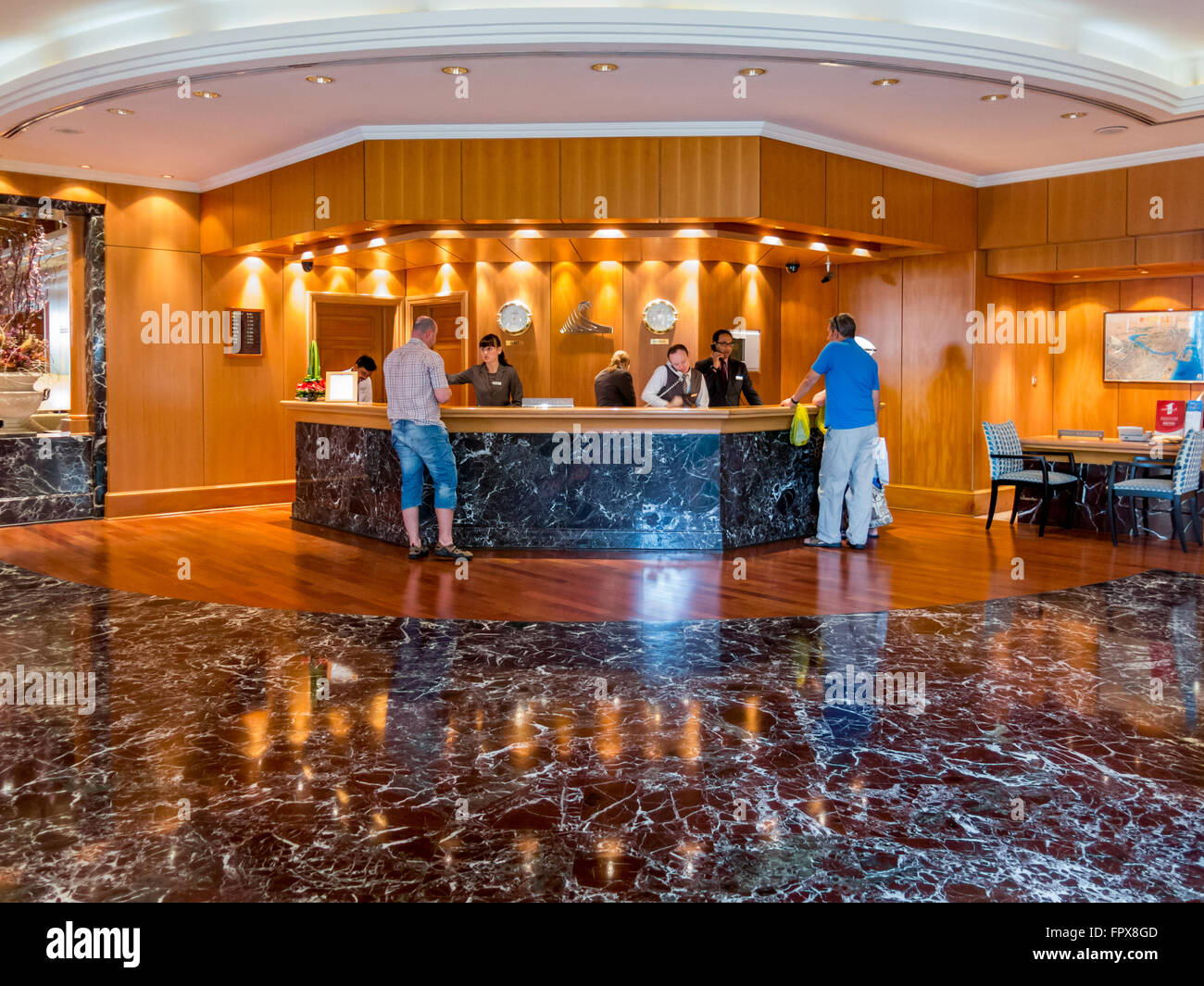 Receptionists and guests at reception desk in hotel beach resort in Dubai, United Arab Emirates - Stock Image