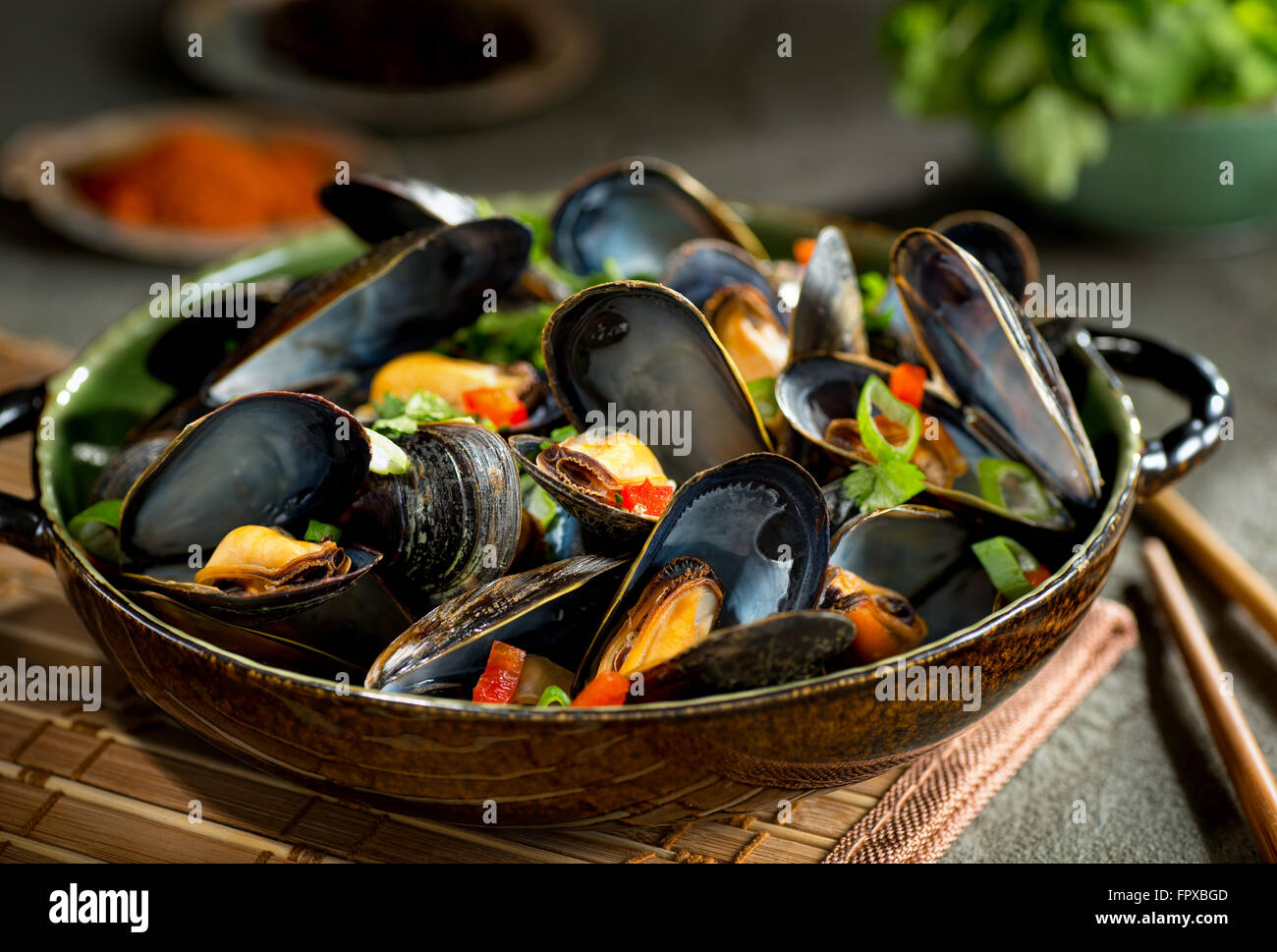 Delicious asian style steamed mussels with red pepper, green onion, and coriander in a coconut broth. - Stock Image