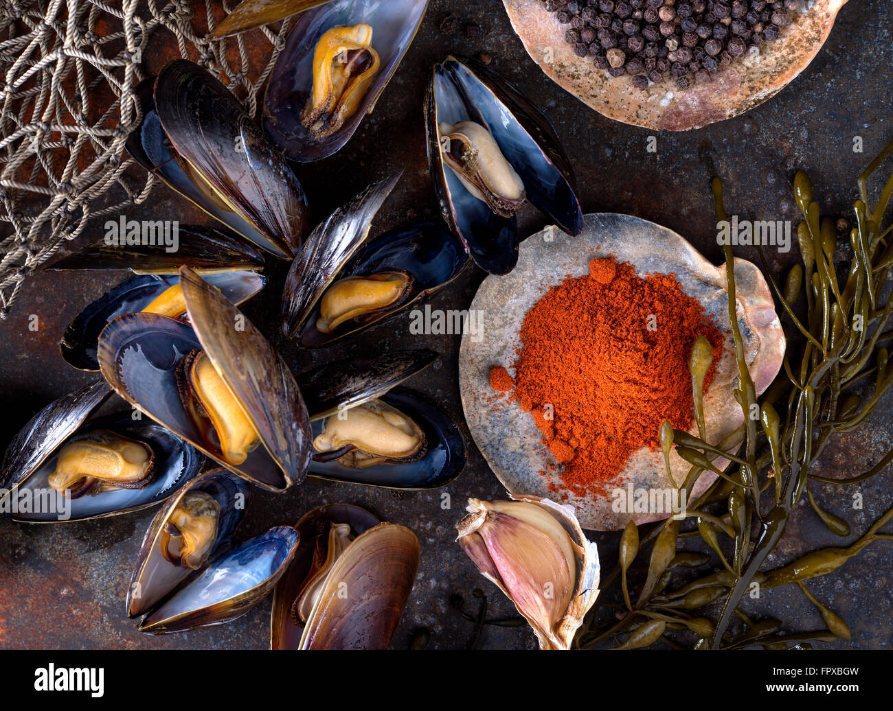 Steamed mussels on a rustic background with paprika, pepper, garlic, and seaweed. - Stock Image