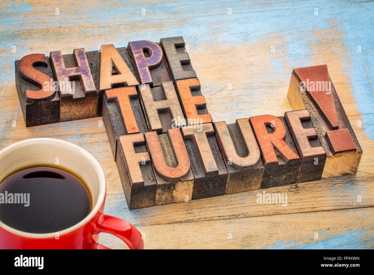 Shape the future - motivational phrase in vintage letterpress wood type blocks stained by color inks - Stock Image