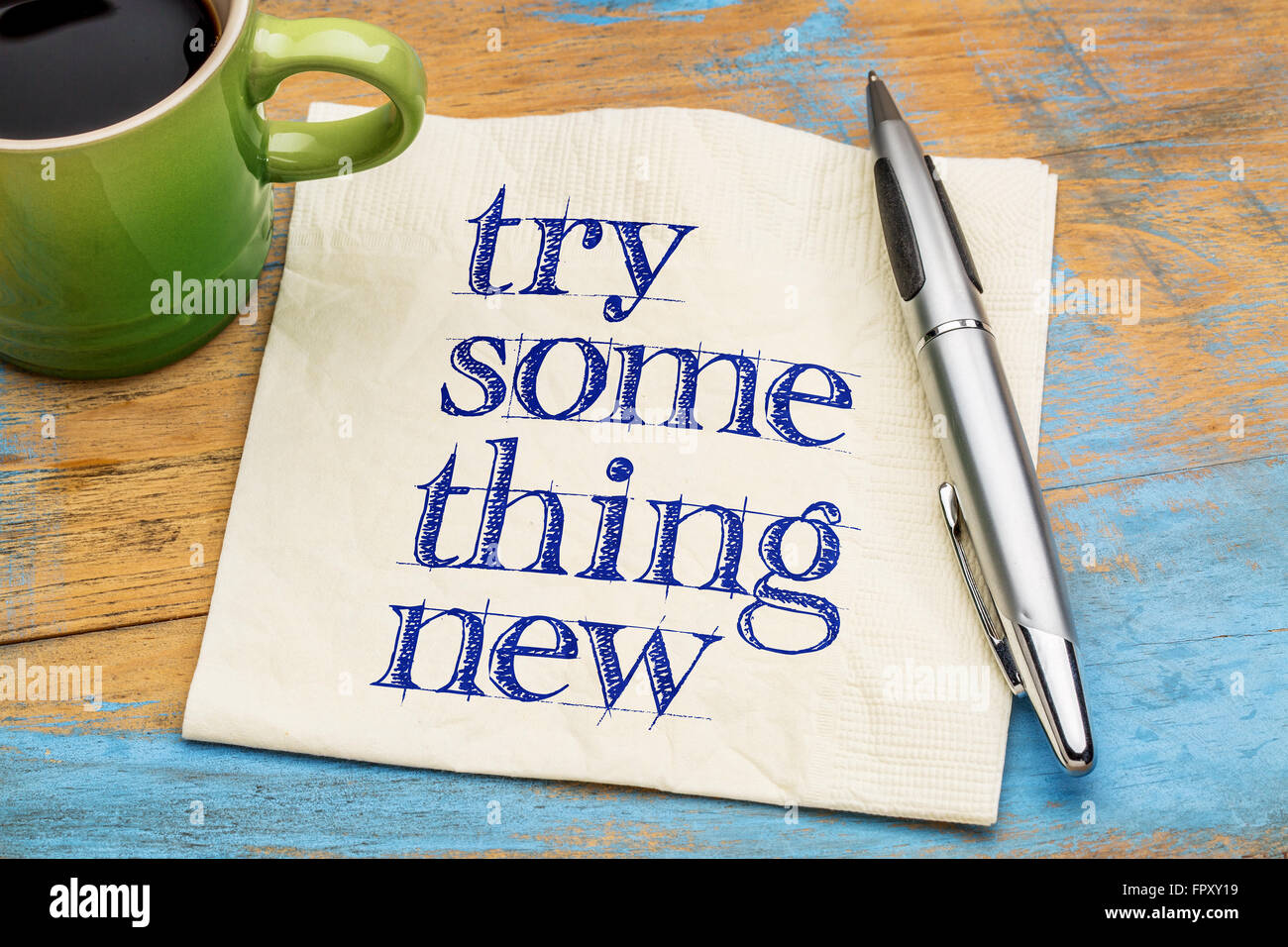 Try something new advice or reminder - handwriting on a napkin with a cup of coffee - Stock Image