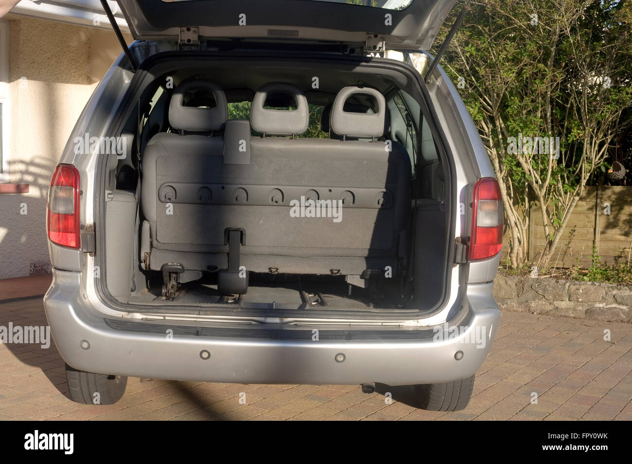 Open tailgate of Chrysler Grand voyager shows boot with luggage space and rearmost seats with headrests - Stock Image