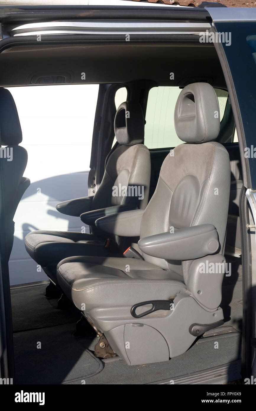 Open middle door of Chrysler grand voyager shows leather seats and spacious interior - Stock Image