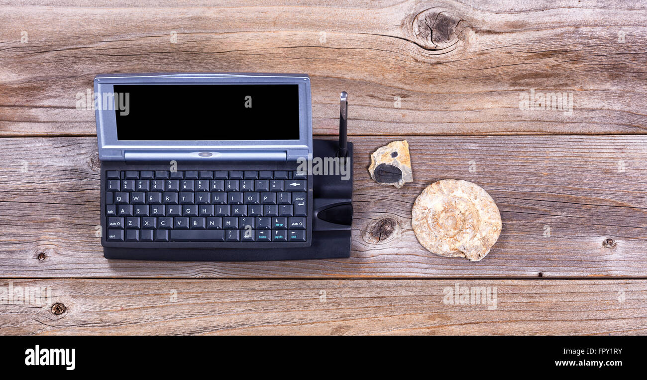 Overhead view of a vintage computer on stressed wood with stone fossils.  Obsolete concept. - Stock Image