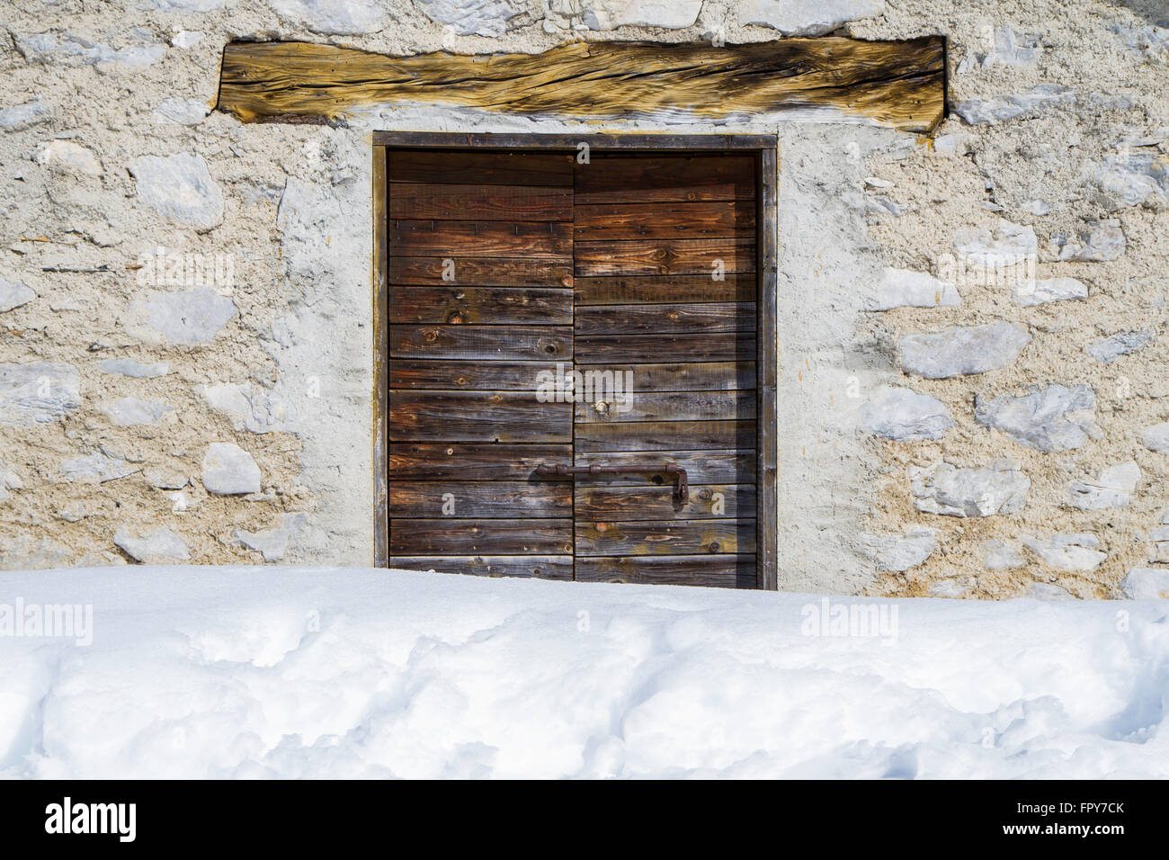 close up of a wooden door of a mountain retreat with snow - Stock Image