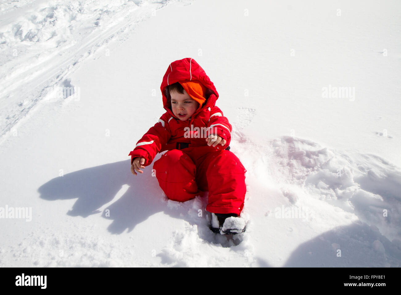 close up child with red ski suit in the snow - Stock Image