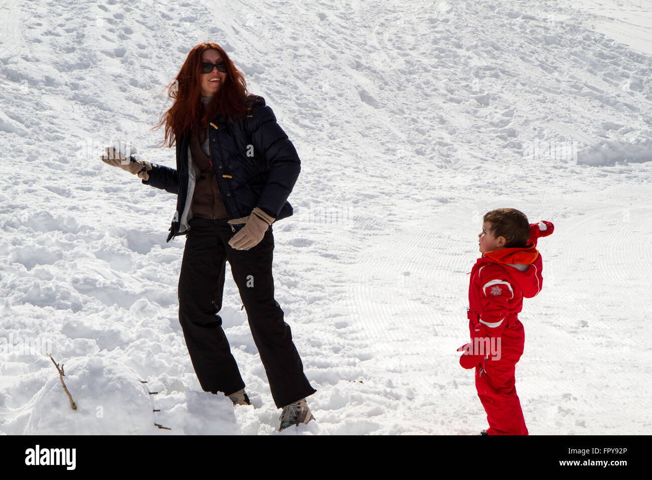 Mom and baby with red ski suit playing snowballs - Stock Image