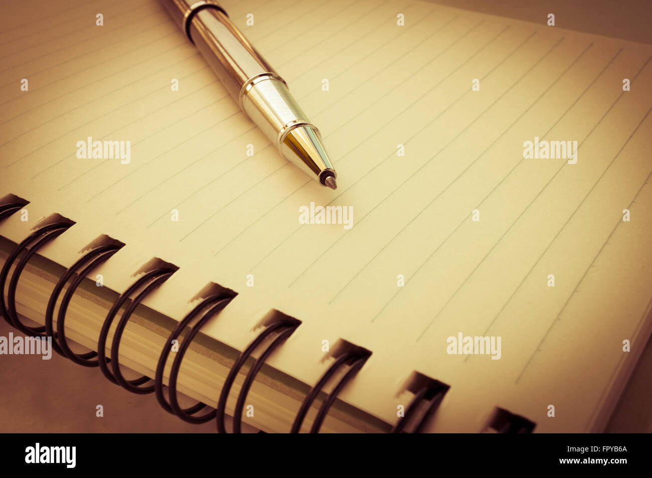 Metallic ball pen on notebook in vintage style.Selective focus. Stock Photo