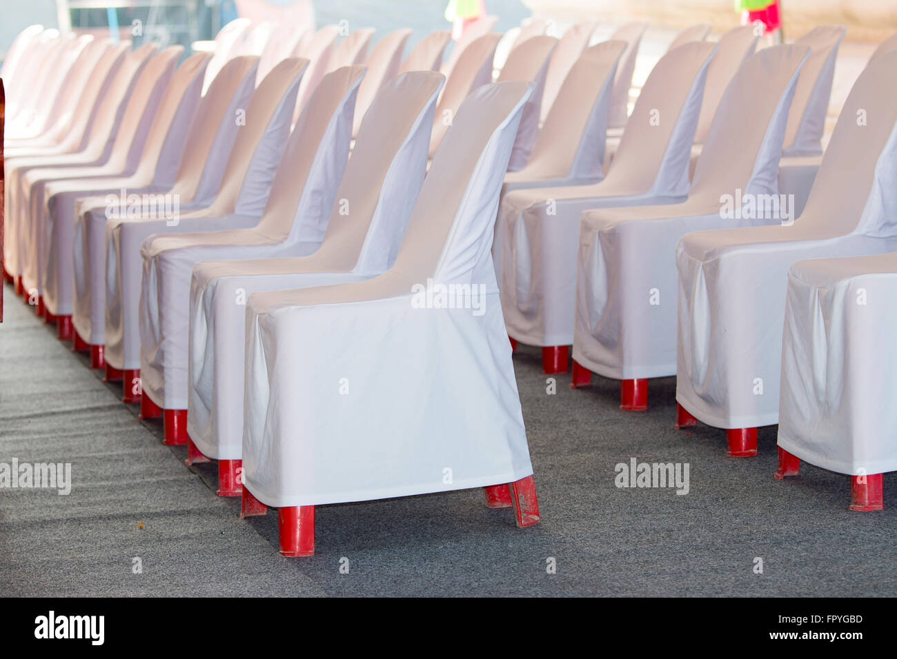 Red Plastic Chairs Were Covered With A White Cloth.