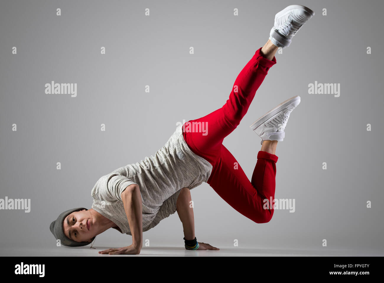 One fit handsome modern style dancer young man in casual red pants and beanie working out, performing breakdance - Stock Image