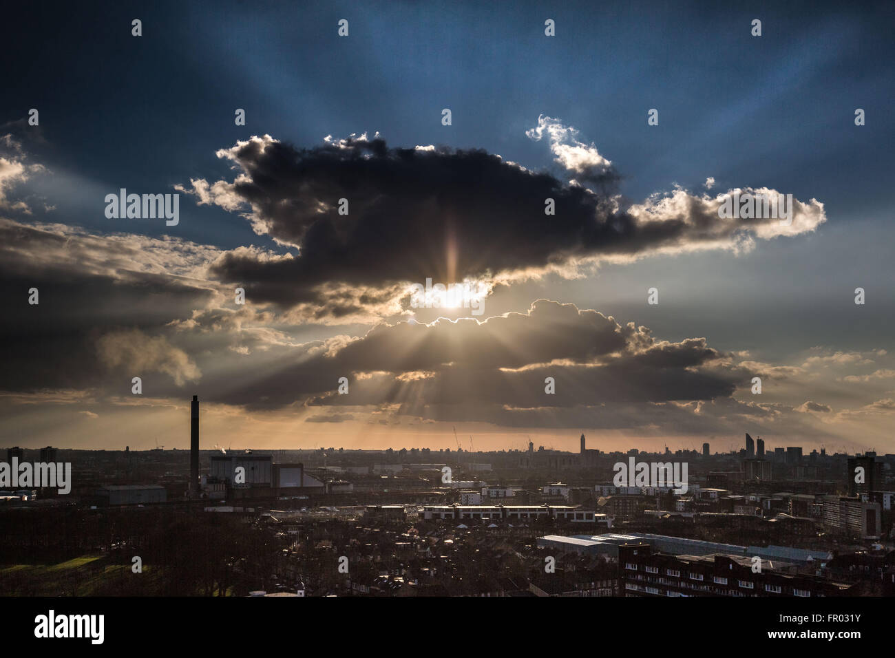 London, UK. 20th March, 2016. UK Weather: Afternoon sun rays burst through clouds over London city just before sunset - Stock Image
