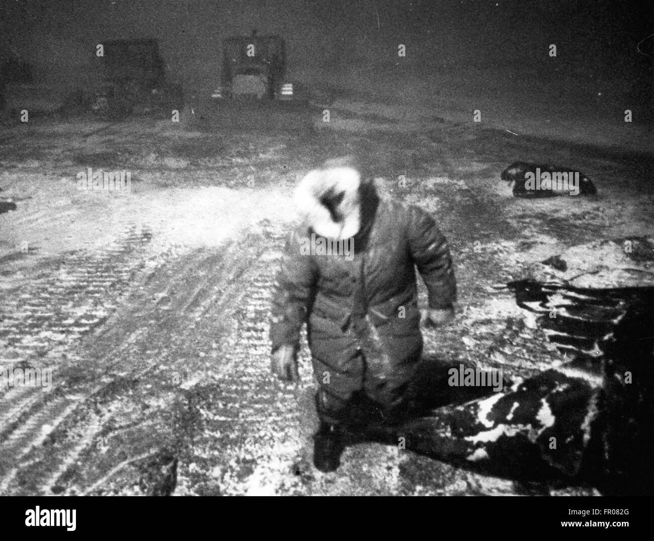 1962 - A member of the transport team returns after refueling a vehicle in a blizzard at a camp near Put River, Stock Photo
