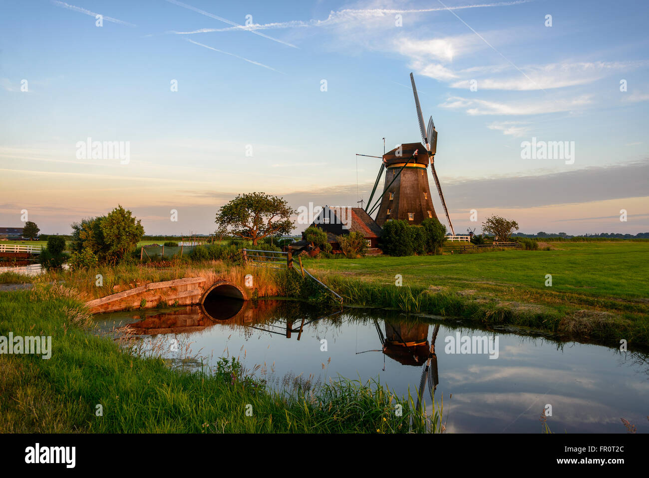 Windmill next to a canal with a bridge in an agricultural area in the countryside in Holland at sunset in Aarlanderveen. - Stock Image