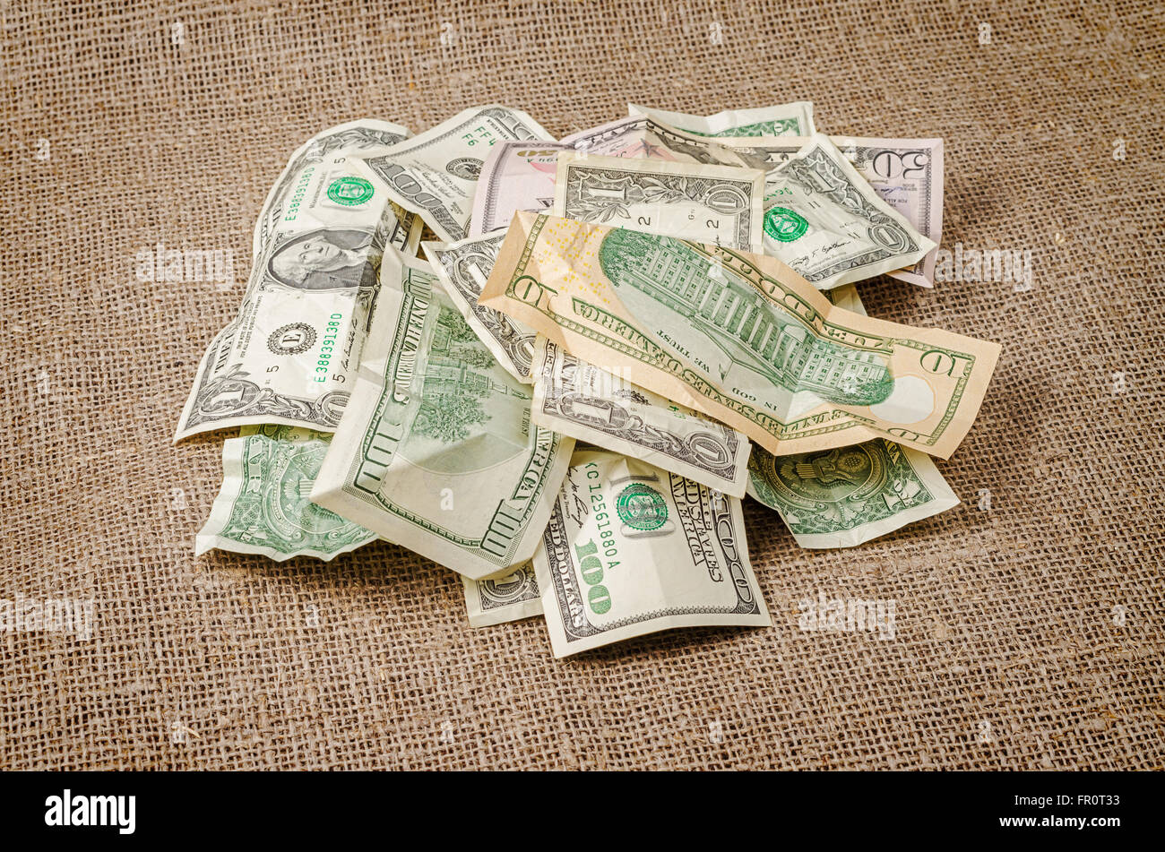 Pile of US dollar banknotes crumpled on rustic jute background - Stock Image