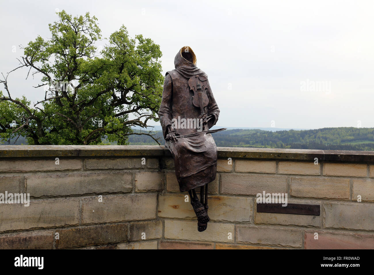 Monk Maurus with a violin sitting on the wall around the church in parish church of St. James in Hohenberg, Germany Stock Photo